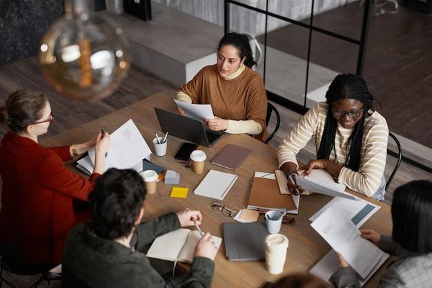 Высокий угол обзора в разнообразной группе деловых людей, встречающихся за столом в графическом интерьере офиса, копией пространства