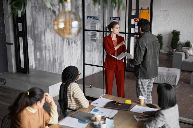 Высокий угол обзора на разнообразную группу деловых людей, работающих в офисе, копировальное пространство