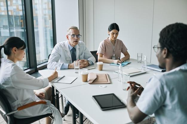 의학 세미나 중 회의실의 회의 테이블에 앉아 있는 다양한 의사 그룹의 높은 각도 보기, 복사 공간