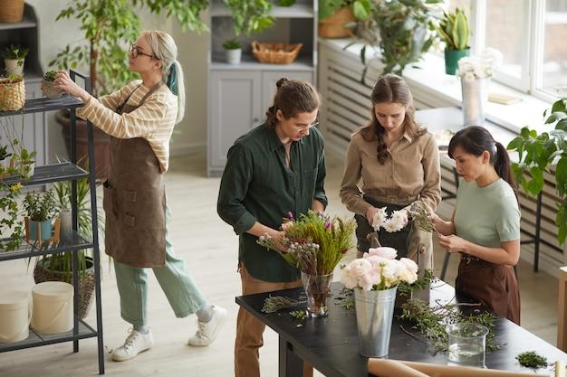 ワークショップクラス、コピースペース中に花の組成物を作成する若い花屋の多様なグループでのハイアングルビュー