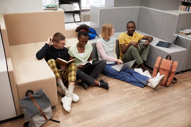 同僚の床に座って一緒に勉強している若い学生の多様なグループのハイアングルビュー...