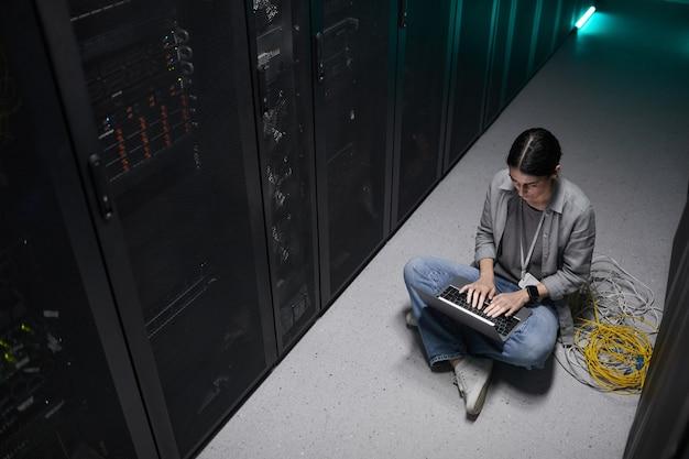 Высокий угол обзора: женщина-инженер-специалист по данным, использующая ноутбук, сидя на полу в серверной и настраивая суперкомпьютерную сеть, копирует пространство