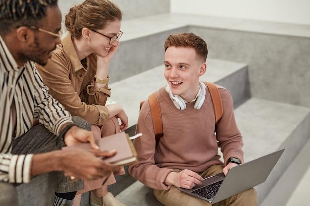 モダンな大学のラウンジで屋内でチャットしている陽気な学生のグループでのハイアングルビュー、友人とラップトップを使用して若い男に焦点を当てる