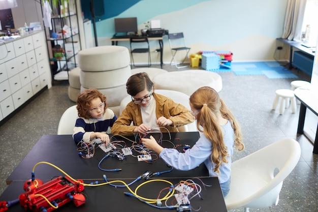 ロボットを構築し、学校の工学の授業で電気回路を実験している子供たちのグループでのハイアングルビュー、コピースペース