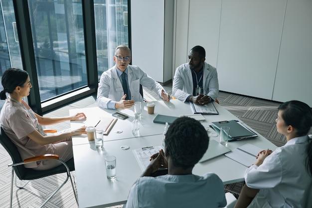 의료 세미나 중 회의실의 회의 테이블에 앉아 있는 의사 그룹의 높은 각도 보기, 복사 공간