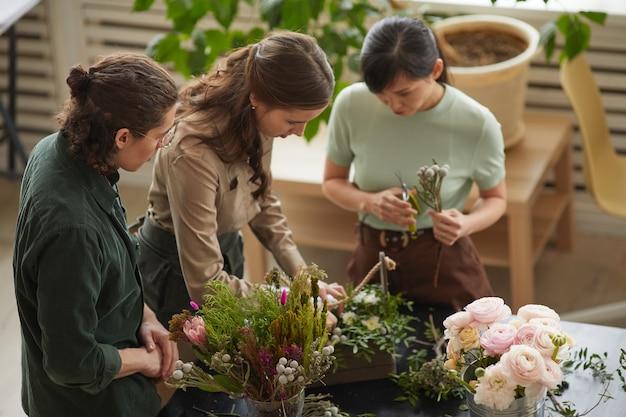 ワークショップ、コピースペースで花の組成物を配置する花屋のグループでのハイアングルビュー