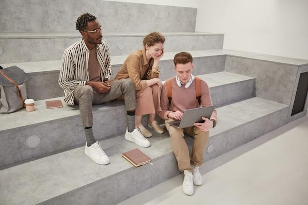 Вид под высоким углом на группу студентов, которые вместе используют ноутбук и болтают в современной гостиной колледжа, скопируйте пространство