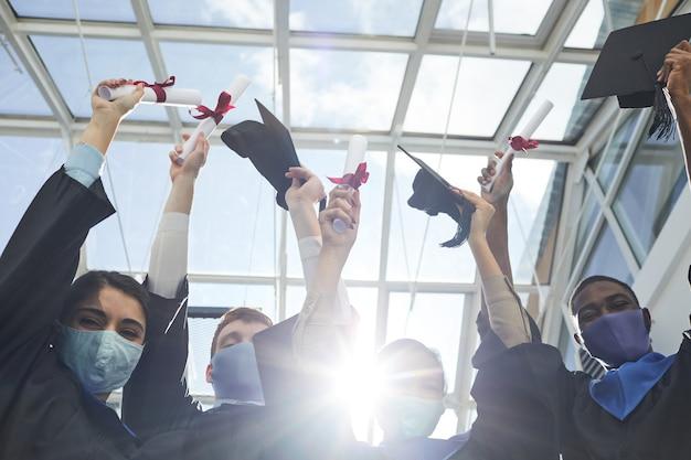 Вид под высоким углом на группу выпускников университета, держащих дипломы, стоя в помещении, освещенном солнечным светом