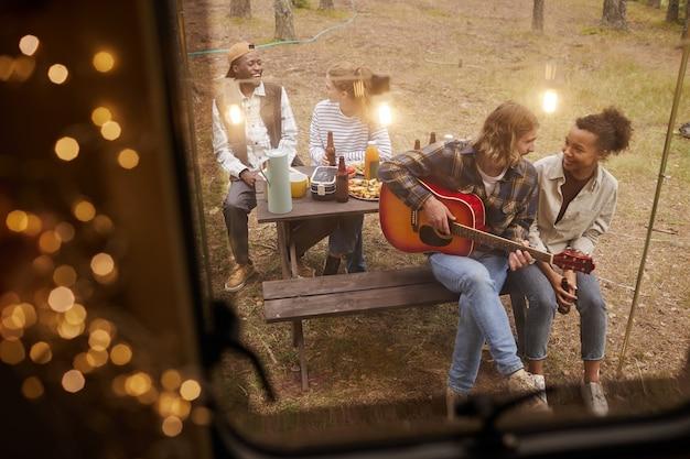 妖精に照らされたバンで野外キャンプをしながらギターを弾く若者たちのグループのハイアングルビュー...