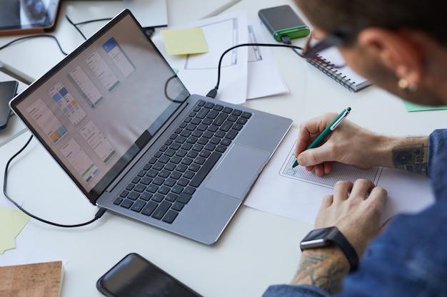 モバイルアプリケーションやウェブサイトのインターフェイスを設計する男性のソフトウェアエンジニアの高角度ビュー、ノートパソコンの画面に焦点を当て、スペースをコピー