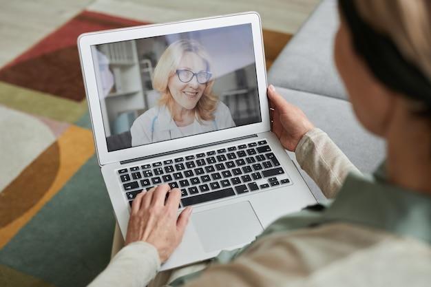 ビデオチャット、コピースペースでノートパソコンの画面で女医師と話している成熟した女性のハイアングルビュー