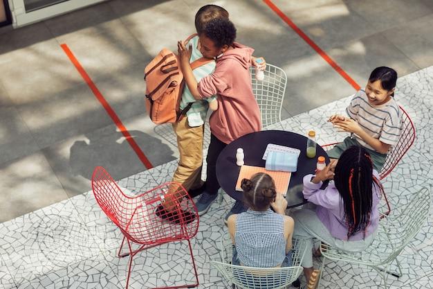 현대 학교에서 점심 시간에 야외 테이블에서 만나는 다민족 어린이 그룹의 높은 각도 보기, 복사 공간