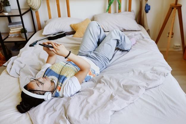 Высокий угол обзора на модную девушку-подростка, лежащую на кровати и использующую смартфон в интерьере уютной комнаты, копирование пространства