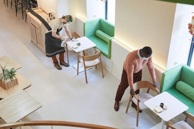 Вид под высоким углом на двух человек, чистящих столы и дезинфицирующих мебель в кафе, готовясь к открытию утром, скопируйте пространство