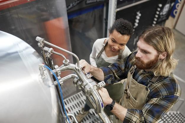 ビール製造工場、コピースペースで醸造設備を操作している2人の若い労働者のハイアングルビュー