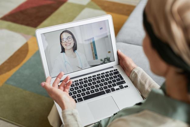 ビデオチャット、コピースペースでノートパソコンの画面で若い女性医師と話している女性のハイアングルビュー