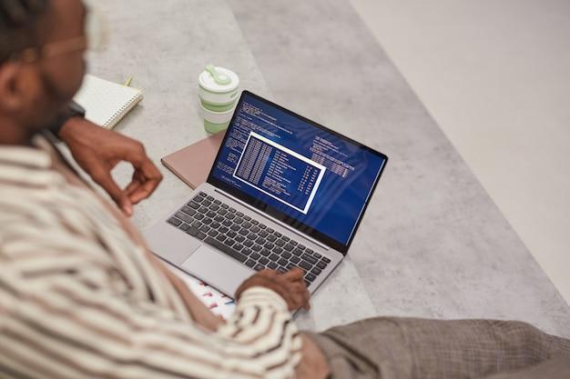 Высокий угол обзора на молодого афроамериканца, использующего ноутбук с it-кодом на экране во время учебы в колледже или работы внештатным сотрудником, скопируйте пространство