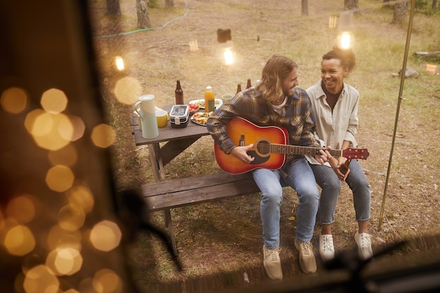 妖精の光の警官に照らされたバンで屋外でキャンプしながらギターを弾く若いカップルのハイアングルビュー...
