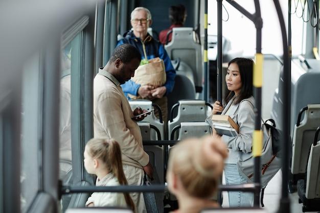 Высокий угол обзора молодой студентки, держащей книгу в автобусе во время поездки на общественном транспорте по городу, копией пространства