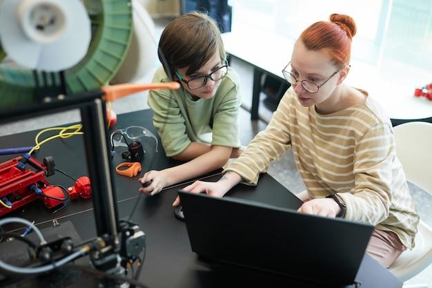 Высокий угол обзора молодой учительницы, помогающей мальчику с помощью 3d-принтера во время урока робототехники и инженерии в школе