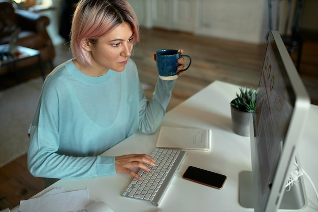 High angle view of attractive young female freelancer having concentrated facial expression while working distantly from home, sitting in front of desktop computer, typing, drinking coffee