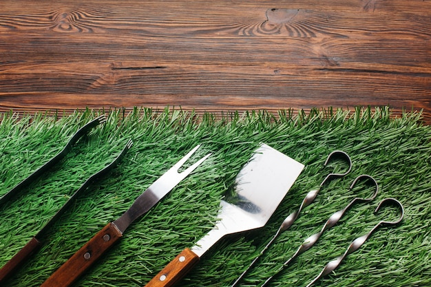 High angle view of barbecue utensil set on green mat over wooden table