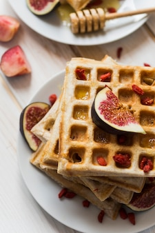 High angle view of belgian waffles; honey with fig fruit in plate