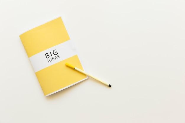 Vista dell'angolo alto del diario di grandi idee con la penna su fondo bianco