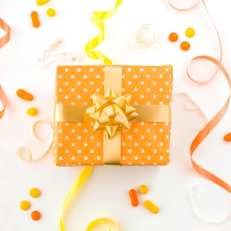High angle view of birthday gift with ribbons and candies on white surface