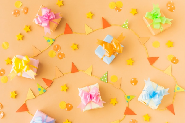 High angle view of birthday gifts and party accessories on colored background