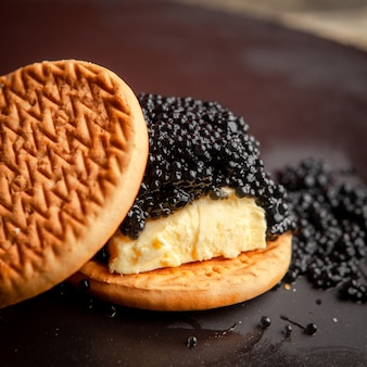 High angle view black caviar between biscuits with butter on dark background.