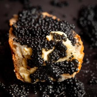 Высокий угол обзора черная икра на хлеб на темном фоне.