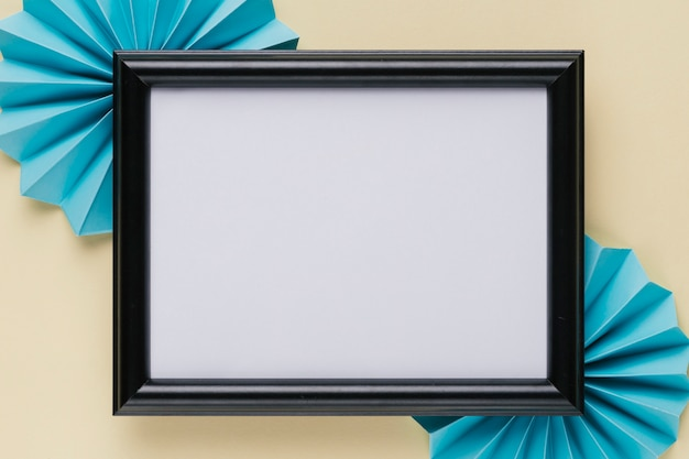 High angle view of black wooden border photo frame with blue origami fan on beige background