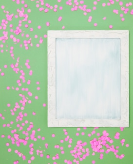 High angle view of blank frame with pink confetti against green background