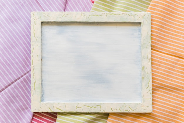 High angle view of blank picture frame on stripes pattern fabrics