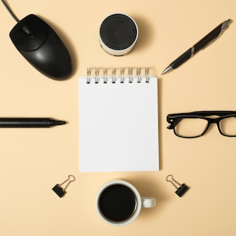 High angle view of blank spiral notepad surrounded by bluetooth speaker; pen; paper clips; coffee cup; eyeglass on beige background