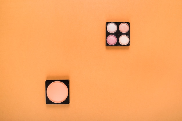 High angle view of blusher and eye shadow powders on orange background