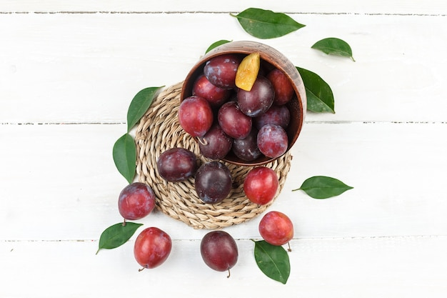 High angle view a bowl of plums on wicker placemat on white wooden board surface. horizontal