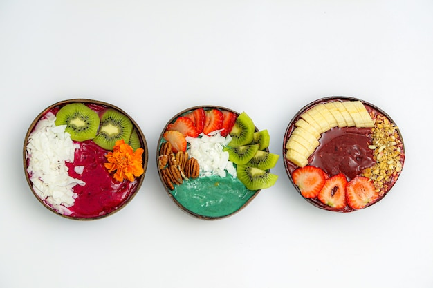 High angle view of bowls with sliced fruits and sauces on the white table