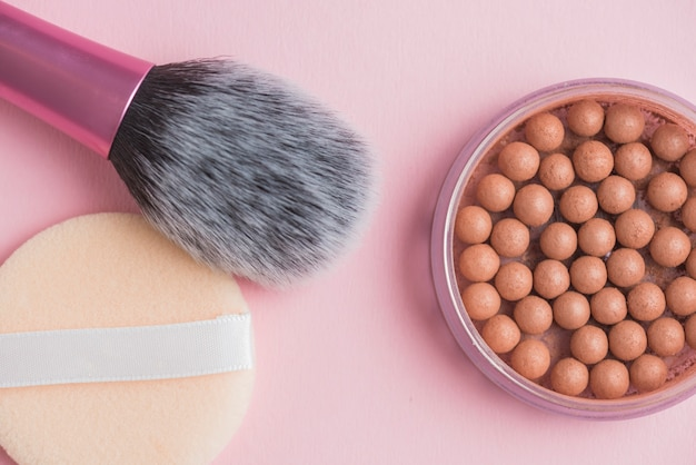 High angle view of bronzing pearls; sponge and makeup brush on pink surface