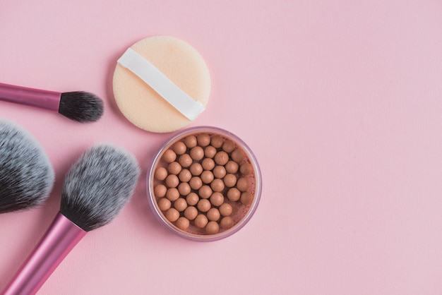 High angle view of bronzing pearls; sponge and makeup brushes on pink surface