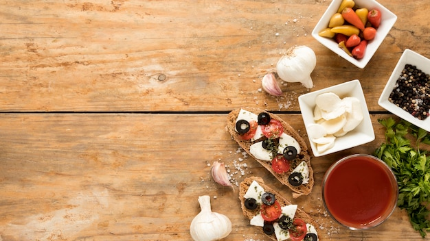High angle view of bruschetta and ingredient on wooden background