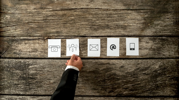 High angle view of businessman laying out white cards with communication and people icons on a rustic wooden background.