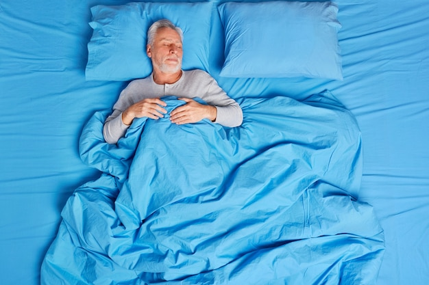 High angle view of calm bearded grey haired senior man sleeps peacefully in bed enjoys pleasant dreams feels tired after hard day lives alone poses on soft blue pillow. early morning concept