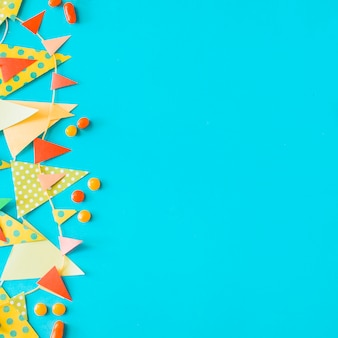 High angle view of candies and bunting on blue background