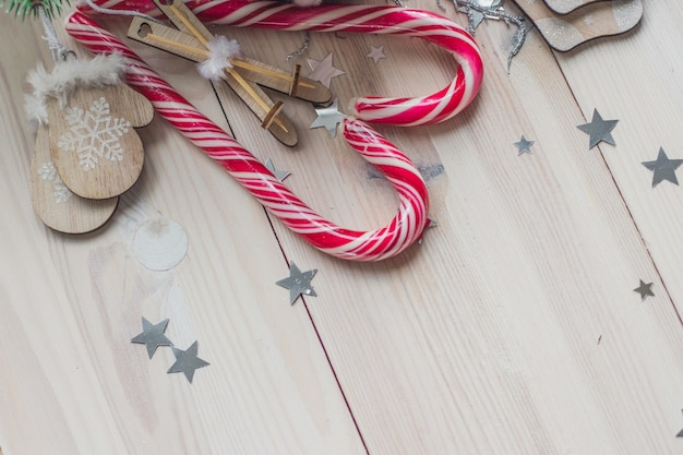 High angle view of candy canes and christmas ornaments on a wooden table under the lights