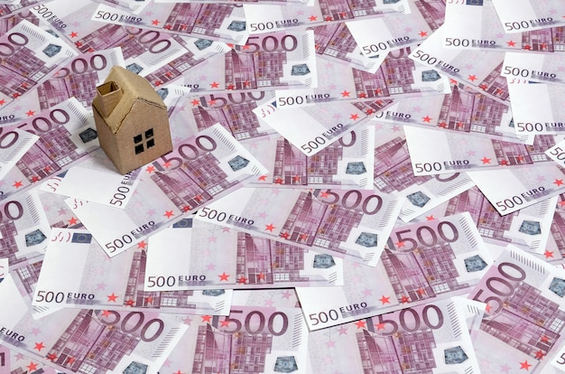 High angle view of a cardboard toy house on 500 euro notes