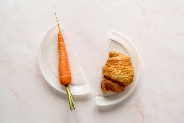 High angle view of carrot and croissant on broken plate