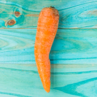 High angle view of carrot on turquoise colored wooden plank