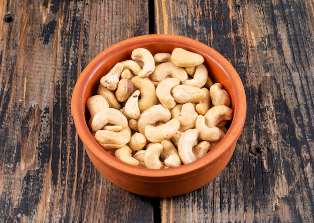 High angle view cashews in pottery on wooden table.